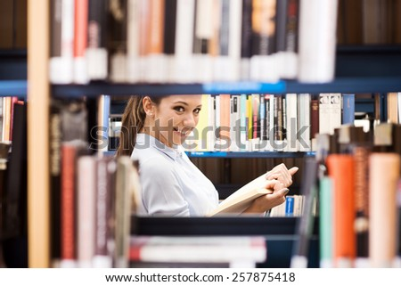 Young student at the library searching for books and peeking through bookshelves