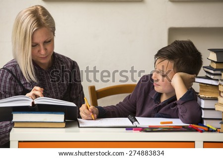 Young student doing homework with a tutor. - stock photo