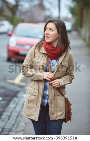 Young student female walk on the side of the street, autumn or spring clothes, blurred street as background