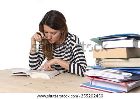 young student girl concentrated studying with textbook at college library desk with piles of books preparing MBA test or exam in academic wisdom and education concept  - stock photo