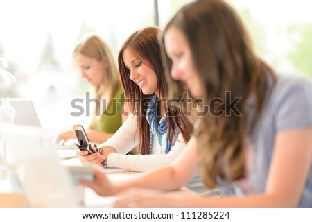 Young student girl in classroom using phone write message - stock photo