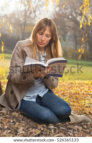 Young student girl reading a book in the park.