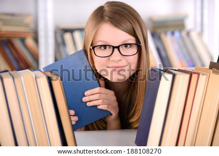 Young student girl with book selection bookshelf, school - stock photo