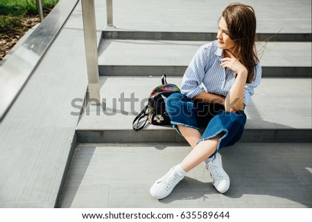 Young student hipster woman with backpack sitting on stairs in city, wearing a striped shirt, blue jeans over shopping or business center background.