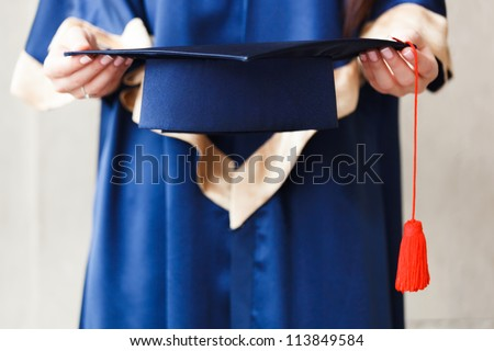 Young student holding academic hat in hands - stock photo