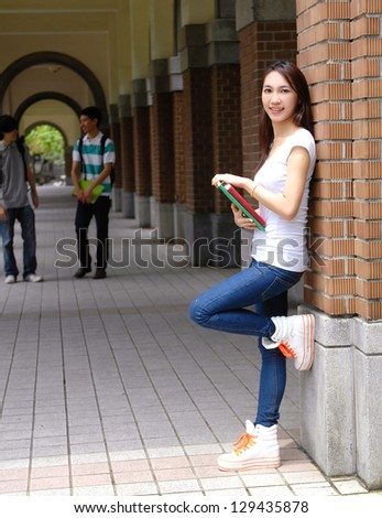 young student holding book at campus - stock photo