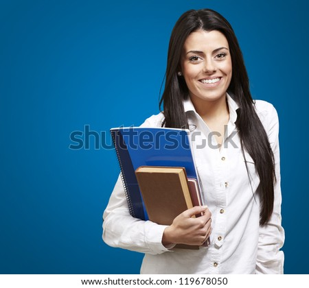 young student holding books and smiling against a blue background