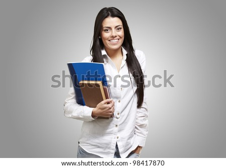 young student holding books and smiling against a grey background - stock photo