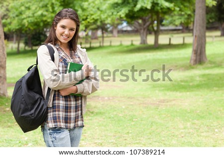 Young student holding textbook while standing in a park - stock photo