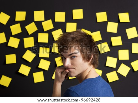 Young student in front of a board with yellow notes and looking in to the camera - stock photo