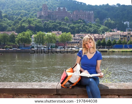 Young student in Heidelberg reading a book  - stock photo