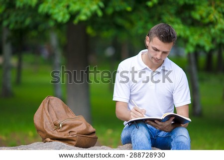 Young student in park outside write down his thoughts in a notebook - stock photo