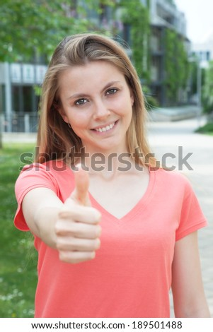 Young student in red shirt showing thumb up - stock photo
