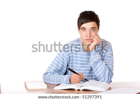 Young student is sitting on desk with open book and learns for his exams. He looks neutral into camera. Isolated on white.