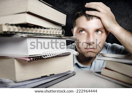 Young student Man in stress Overwhelmed , overworked and frustrated among a pile of books and notebooks studying for exam on desk in college and university education concept