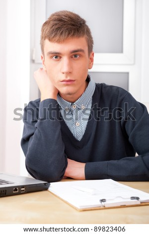 Young student man working in bright room, sitting at desk, using laptop and papers - stock photo