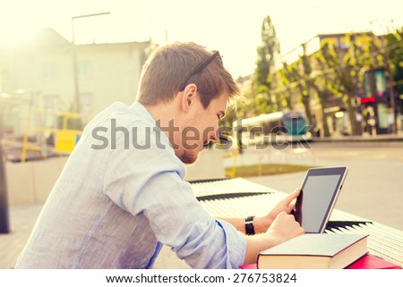 Young student men taping on tablet in a city on university bench .Young student  outdoors with tablet.Life style.City - stock photo