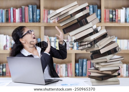 Young student of business management hold a pile of falling books in the library - stock photo