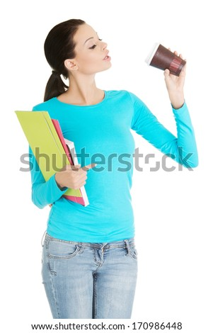 Young student or businesswoman with notebooks drinking coffee or tea from paper mug