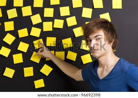 Young student pointing to a board full of yellow notes and looking in to the camera - stock photo