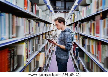 young student reading book between the shelves in the library - stock photo