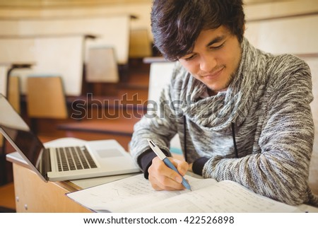 Young student sitting at a desk writing notes in the classroom - stock photo
