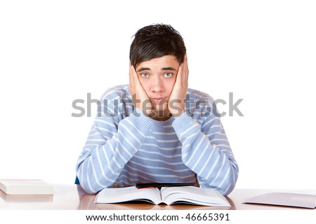 Young student sitting on desk and learns for his exams. He looks sad and tired into camera. Isolated on white.