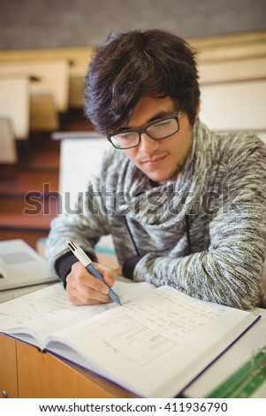 Young student sitting on desk reading notes in the classroom - stock photo