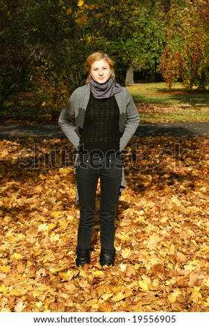 Young student standing in the middle of golden leaves under a tree