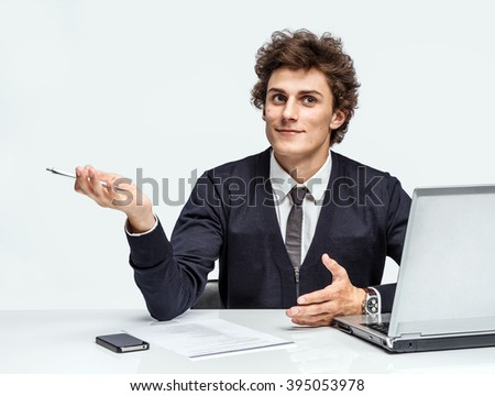 Young student thinking while writing notes. Man at the workplace working with computer on gray background. - stock photo