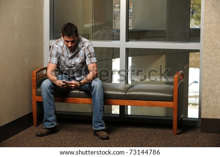 Young Student using his cell phone to text at the College Campus - stock photo