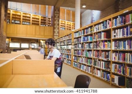 Young student using his laptop in college library - stock photo