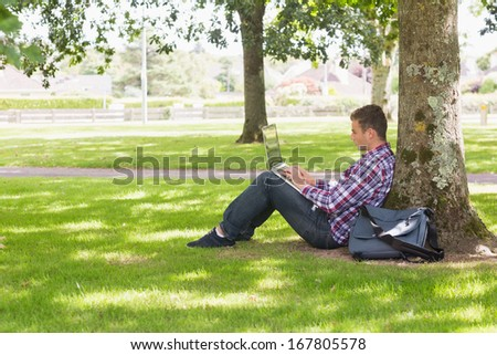 Young student using laptop outside on college campus - stock photo