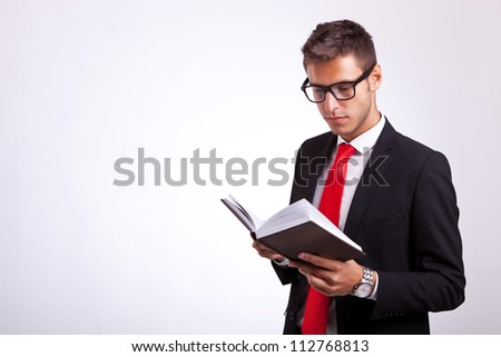 young student wearing glasses and reading a law book on grey background