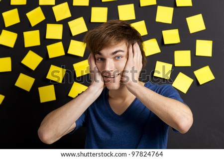 Young student with a funny expression in front of a board full of yellow notes - stock photo