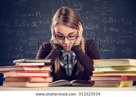 Young student with desperate expression sitting at a desk and looking at her books - stock photo