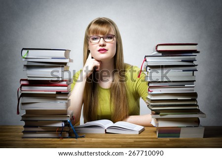 Young student with glasses sitting at a table with many books - stock photo