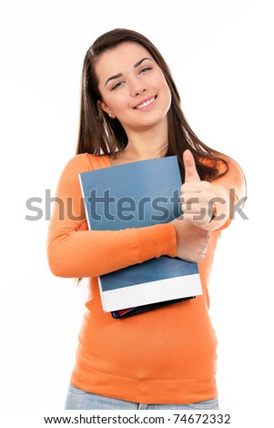 Young student with her books in hand giving thumb-up gesture, smiling and looking at the camera - stock photo