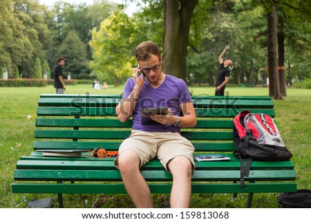 Young student with tablet and mobile phone sitting on a bench. - stock photo