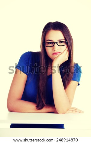 Young student woman bored, sitting by the desk. - stock photo