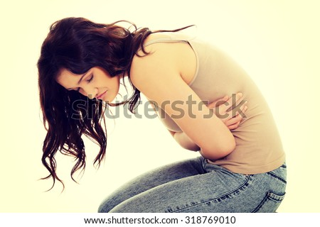 Young student woman curled up with a huge stomachache. - stock photo