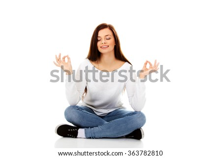 Young student woman sitting and doing yoga - stock photo
