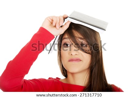 Young student woman with notebook on head. - stock photo