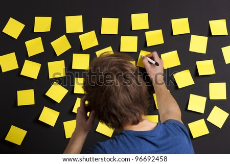 Young student writing a message on a yellow note - stock photo