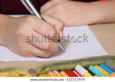 Young student writing in his exercise book at school - stock photo