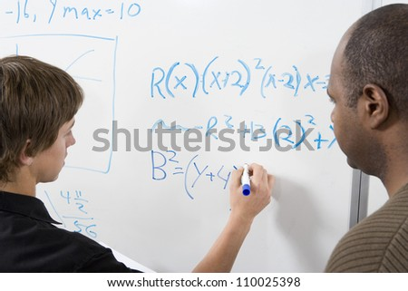Young student writing math sums on board - stock photo