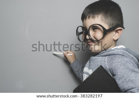 young student writing on a blackboard school with a book in hand and big glasses