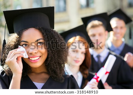 Young students dressed in black graduation gown. Campus as a background. Afro American girl crying, smiling, holding diploma and looking aside. Students are on background standing in row - stock photo