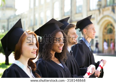Young students dressed in black graduation gown. Campus as a background. Students standing in row, smiling, holding diplomas and looking straight ahead. Focus on Afro American girl - stock photo