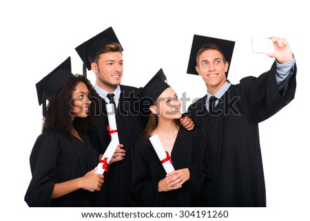 Young students dressed in black graduation gowns. Isolated on white background. Students holding diplomas, smiling and making photo on phone